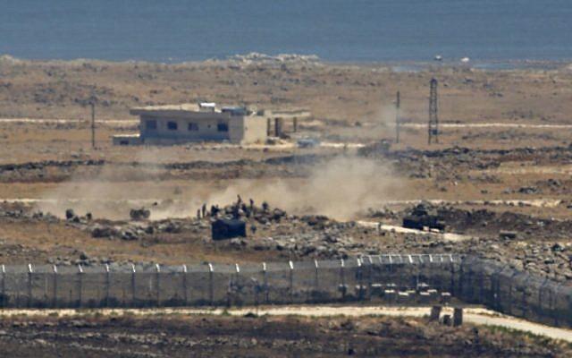 Una imagen tomada el 16 de julio de 2018 de los Altos del Golán israelí muestra cómo los combatientes rebeldes sirios junto a un tanque y un arma de artillería se acumulan cerca de la frontera en la provincia de Quneitra, al sureste de Siria, mientras las fuerzas del gobierno presionan su asalto sobre el área. (AFP Photo / Jalaa Marey)
