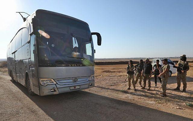 Los miembros del grupo Hayat Tahrir al-Sham, liderados por el ex afiliado de Al Qaeda en Siria, miran cómo los autobuses se preparan para ingresar a las ciudades de Fuaa y Kefraya para evacuar a sus residentes el 18 de julio de 2018 (AFP PHOTO / OMAR HAJ KADOUR)