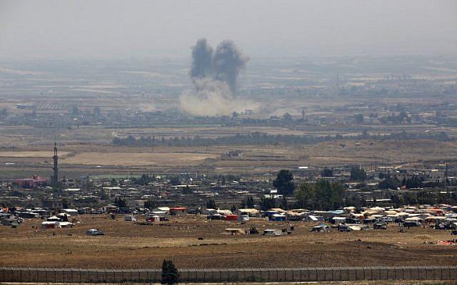 Una imagen tomada el 18 de julio de 2018 de los Altos del Golán israelí muestra humo que se eleva sobre los edificios durante ataques no identificados a través de la cerca fronteriza frente a un campamento para sirios desplazados cerca de la aldea de al-Rafeed en la provincia sureña siria de Daraa. (AFP PHOTO / JALAA MAREY)
