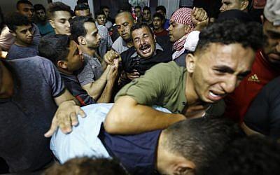 Los familiares palestinos reaccionan cuando llegan a la morgue del hospital al-Shifa en la ciudad de Gaza, donde llevaron el cadáver de Mohammed Badwan después de que las fuerzas israelíes lo mataron a tiros durante las protestas en la frontera al este de la ciudad de Gaza. (AFP PHOTO / ANAS BABA)
