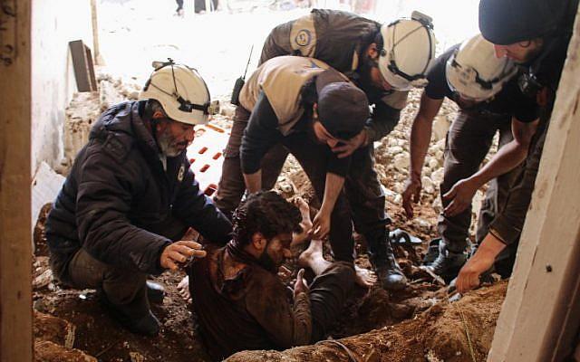 Los miembros de los voluntarios de la Defensa Civil siria, también conocidos como Cascos Blancos, sacaron a una víctima de los escombros de su casa, luego de un ataque aéreo de las fuerzas gubernamentales en una zona controlada por los rebeldes en la ciudad siria sureña de Daraa, el 8 de abril. 2017. (Mohamad ABAZEED / AFP)