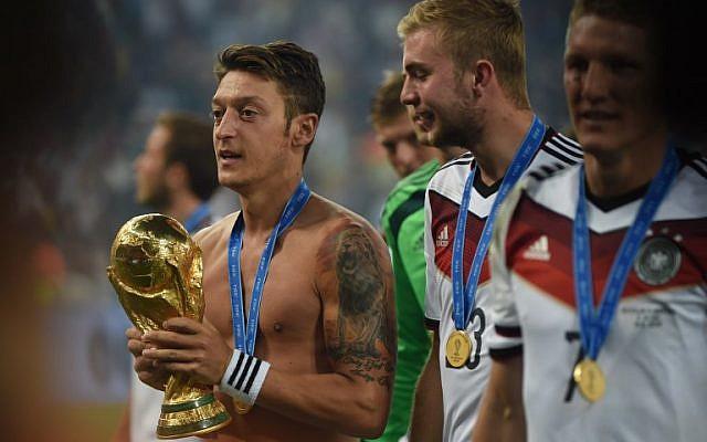 El centrocampista alemán Mesut Ozil, a la izquierda, celebra el trofeo de la Copa del Mundo después del partido de fútbol final entre Alemania y Argentina para la Copa Mundial de la FIFA en el Estadio Maracaná en Río de Janeiro, 13 de julio de 2014. (Patrik STOLLARZ / AFP)