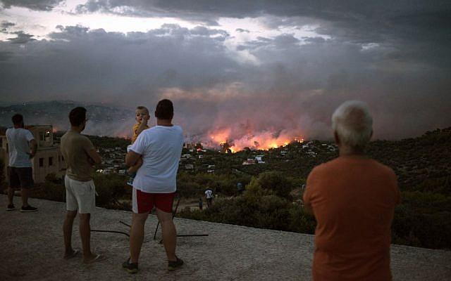 La gente mira un incendio forestal en la ciudad de Rafina, cerca de Atenas, Grecia, el 23 de julio de 2018. (ANGELOS TZORTZINIS / AFP)
