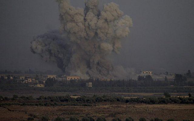 Una fotografía tomada el 25 de julio de 2018 desde la colina Tal Saki en los Altos del Golán muestra humo que se eleva sobre los edificios al otro lado de la frontera en Siria durante los ataques aéreos que respaldan una ofensiva liderada por el gobierno sirio en la provincia sureña de Quneitra. (AFP / JALAA MAREY)