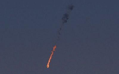Un avión de combate sirio se ve en llamas después de que fue alcanzado por el ejército israelí sobre los Altos del Golán el 23 de septiembre de 2014. (Crédito de la foto: AFP / JALAA MAREY)