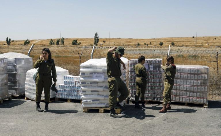Los soldados de las FDI se encuentran junto a los suministros de alimentos que se preparan como ayuda humanitaria para los sirios afectados por la guerra civil en su país, el 19 de julio de 2017. (AFP / MENAHEM KAHANA)