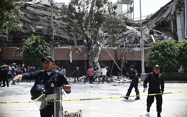 Oficiales de policía acordonaron una calle después de que un edificio colapsó durante un terremoto en la Ciudad de México el 19 de septiembre de 2017. (AFP Photo / Ronaldo Schemidt)