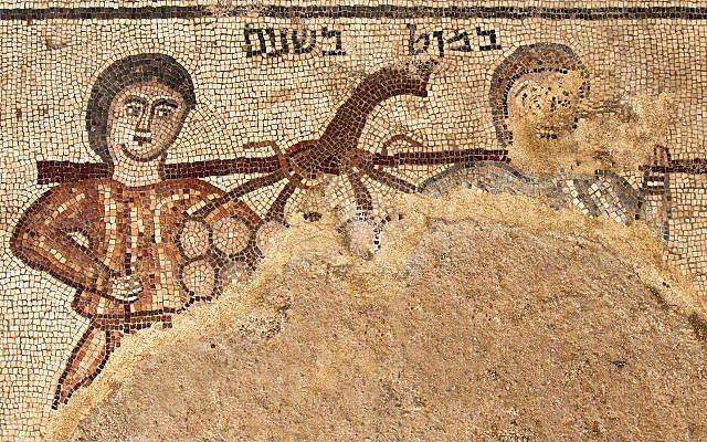 Un mosaico encontrado en la excavación Huqoq de 2018 está etiquetado como 'un polo entre dos', que representa una escena bíblica de Números 13:23. Las imágenes muestran dos espías enviados por Moisés para explorar Canaán llevando un palo con un racimo de uvas. (Jim Haberman)