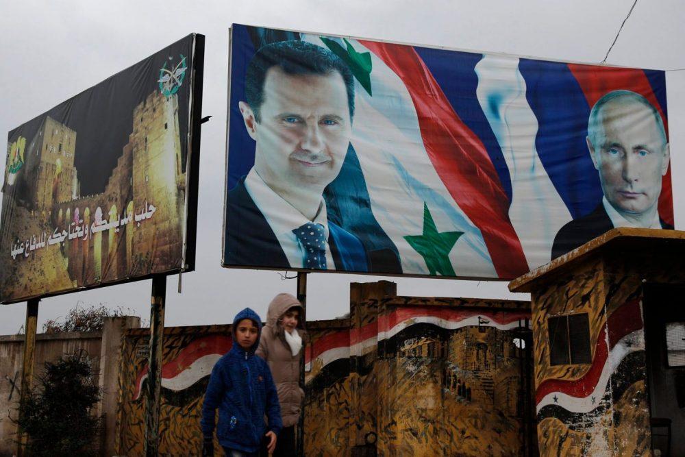Caminata siria por carteles del presidente sirio Bashar Assad y el presidente ruso Vladimir Putin en Aleppo, Siria, el jueves 18 de enero de 2018. Crédito: Hassan Ammar / AP