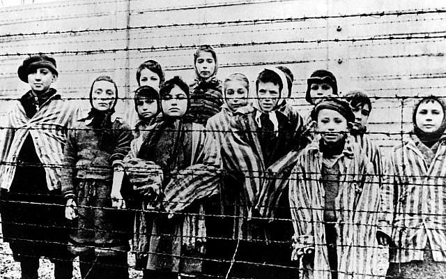 Un grupo de niños vestidos con uniformes de los campos de concentración detrás de alambradas de púas en el campo de concentración nazi de Oswiecim (Auschwitz), fotografiados justo después de la liberación por el ejército soviético, en enero de 1945. (AP Photo / File)