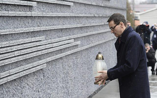 El primer ministro polaco Mateusz Morawiecki coloca una vela en una pared conmemorativa con los nombres de algunos de los polacos que salvaron judíos durante el Holocausto, en el Museo de la Familia Ulma que rescató a los judíos durante la Segunda Guerra Mundial, en Markowa, Polonia, el viernes 2 de febrero. 2018. (AP / Alik Keplicz)