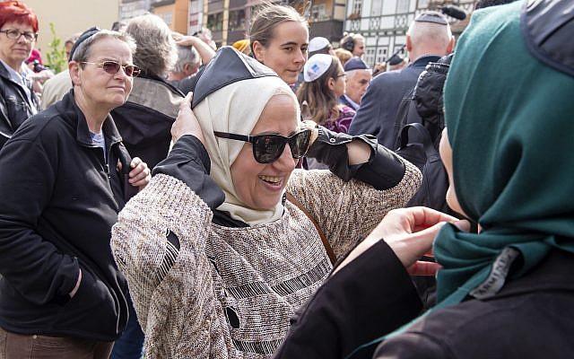 La mujer musulmana Samar Allaham, en el centro, arregla la kippa judía en su cabeza además de la mujer musulmana Iman Jamous, derecha, durante una manifestación contra el antisemitismo en Alemania en Erfurt, Alemania, el 25 de abril de 2018. (AP Photo / Jens Meyer)