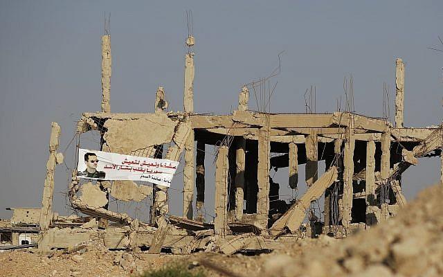 """Un cartel del presidente Bashar Assad con árabe que dice """"Hemos vivido y vivimos para que Siria pueda vivir en el corazón de Bashar Assad"""" se cuelga de las ruinas de una casa que fue destruida durante la lucha entre las fuerzas del gobierno sirio y los insurgentes, en la ciudad de Ain Terma, en el suburbio oriental de Ghouta en Damasco, Siria, 15 de julio de 2018. (Hassan Ammar / AP)"""
