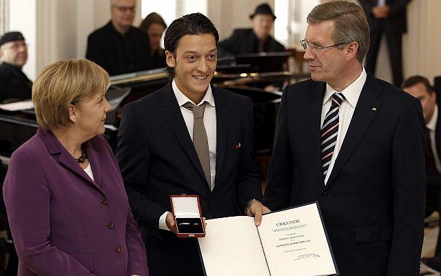 Mesut Ozil, del equipo nacional de fútbol de Alemania, recibe la Hoja de Laurel de Plata de la República Federal del Presidente alemán Christian Wulff, derecha, y la Canciller alemana Angela Merkel, izquierda, en Berlín, Alemania, el martes 5 de octubre de 2010. (AP Photo / Michael Sohn)