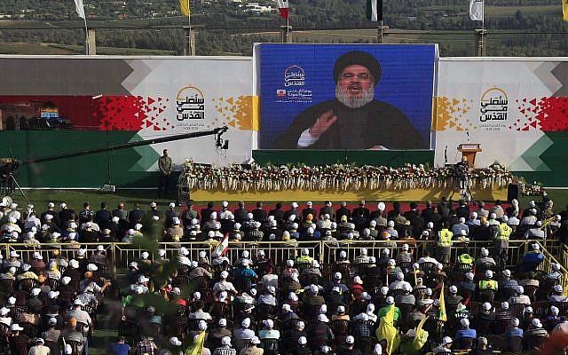 Partidarios de Hezbollah escuchan al líder Hassan Nasrallah pronunciar un discurso en una pantalla de televisión gigante desde un lugar secreto, durante una manifestación para conmemorar el Día de Al-Quds, en la aldea de Maroun el-Rass en la frontera entre Líbano e Israel, sur de Líbano, el viernes. 8 de junio de 2018. (AP Photo / Mohammed Zaatari)