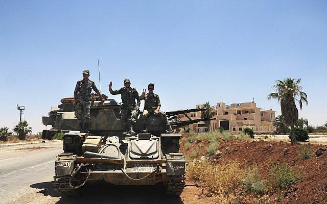 Soldados sirios mostrando el signo de la victoria mientras se sientan en su vehículo militar en el paso fronterizo de Naseeb con Jordania, en la provincia sureña de Daraa, Siria, el 7 de julio de 2018. (SANA vía AP)