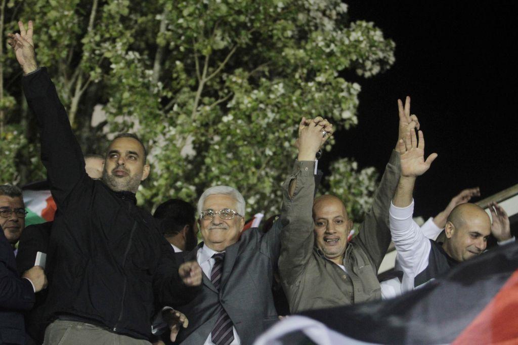 El presidente de la Autoridad Palestina, Mahmoud Abbas, segundo desde la izquierda, saluda con terroristas liberados provenientes de cárceles israelíes durante las celebraciones en la sede de Abbas en la ciudad de Ramallah, 30 de octubre de 2013. (Issam Rimawi / Flash 90)