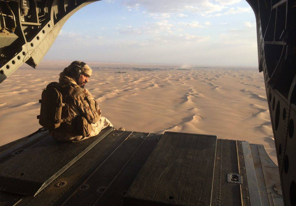 Un artillero emiratí observa el fuego enemigo desde la puerta trasera de un helicóptero militar Chinook de los Emiratos Árabes Unidos sobrevolando Yemen.(AP Photo / Adam Schreck, Archivo)