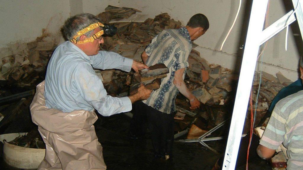 Los voluntarios intentan recuperar el material de archivo judío iraquí del sótano inundado de Mukhabarat, cuartel general de inteligencia de Saddam Hussein, 2003. (Harold Rhode, cortesía de los Archivos Nacionales de los EE. UU.)