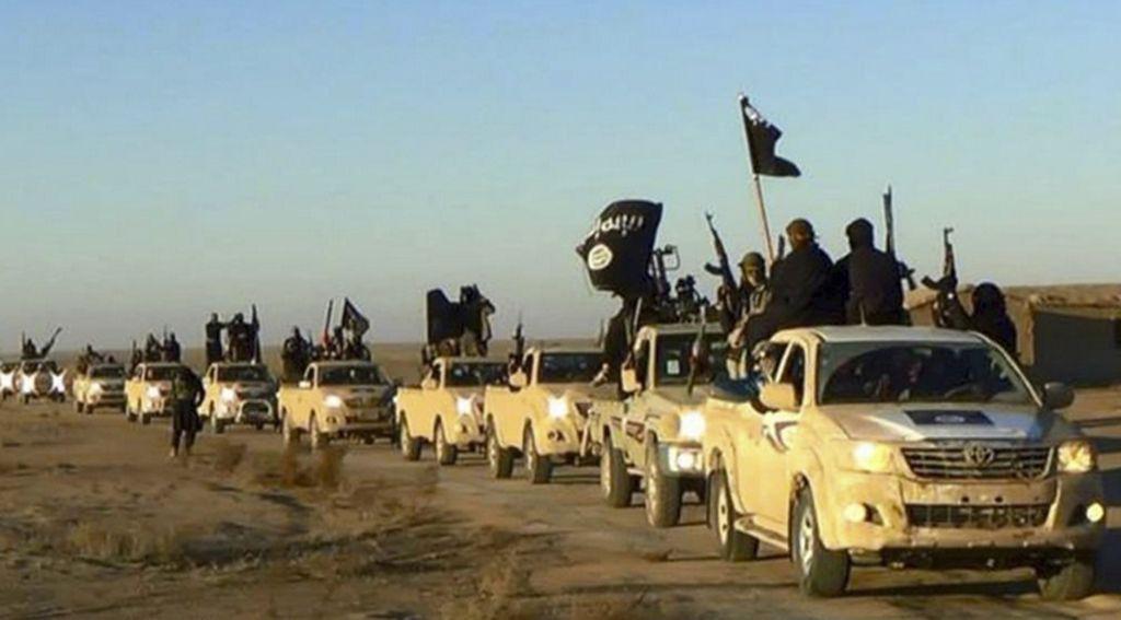 En esta foto sin fecha publicada por un sitio web militante, que se ha verificado y es coherente con otros informes de AP, los militantes del grupo Estado Islámico levantan sus armas y agitan banderas en sus vehículos, en un convoy en una carretera que conduce a Iraq, desde Raqqa, Siria.(Sitio web militante a través de AP)