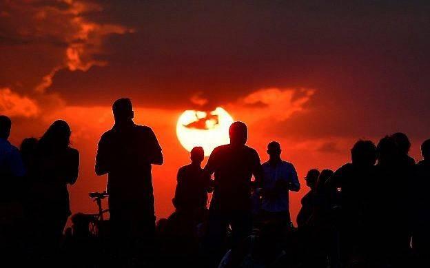 """La gente se reúne mientras esperan que se ponga el sol y la aparición de la """"luna de sangre"""" en Berlín el 27 de julio de 2018. (AFP / Tobias Schwarz)"""