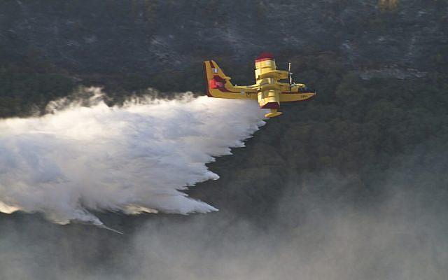 Un avión griego de extinción de incendios rocía material extintor sobre el incendio forestal en llamas en las montañas Carmel, cerca de la ciudad norteña de Haifa, Israel, el 5 de diciembre de 2010. (Doron Horowitz / FLASH90)