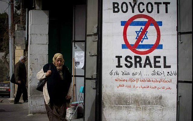 Una mujer palestina camina junto a un letrero que llama a boicotear a Israel en la ciudad cisjordana de Belén el 11 de febrero de 2015. (Miriam Alster / Flash 90)