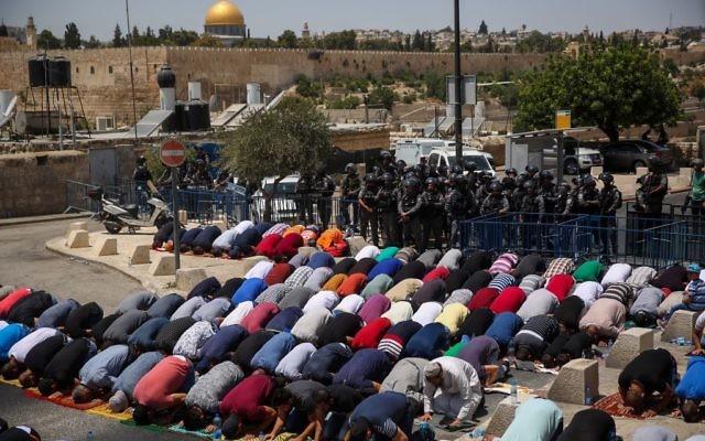 Los musulmanes rezan mientras los policías israelíes vigilan durante las oraciones del viernes en el barrio de Jerusalem Este de Ras el Amud, en las afueras de la Ciudad Vieja, el 28 de julio de 2017 (Hadas Parush / Flash90)