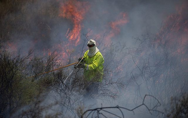Una foto ilustrativa de un bombero que apagaba un incendio en un campo cerca de la Franja de Gaza que fue provocado por un objeto flameado que volaba desde el enclave palestino, el 5 de junio de 2018. (Yonatan Sindel / Flash90)