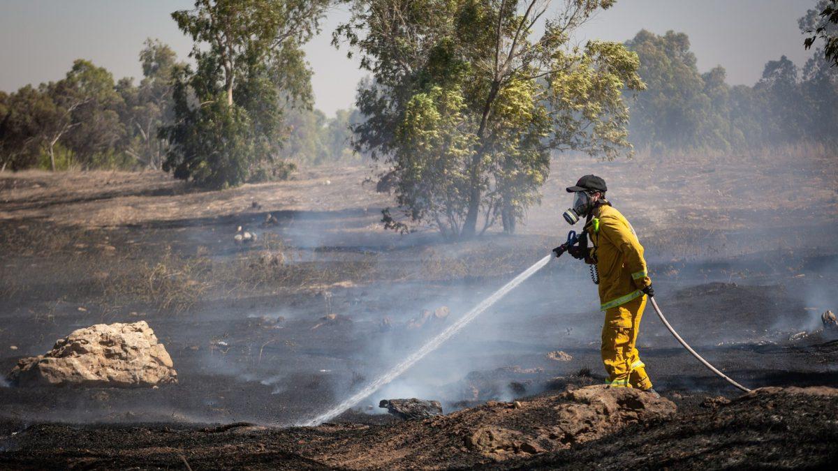 Los bomberos apagan un incendio en un campo causado por bombas incendiarias atadas a cometas voladas por los palestinos, desde la Franja de Gaza, el 27 de junio de 2018. (Flash90)
