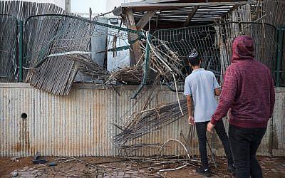 Personas en la escena donde un patio de una casa fue alcanzado por un cohete de Gaza en la ciudad de Sderot, al sur de Israel, el 14 de julio de 2018. (Hadas Parush / Flash90)