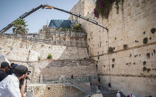 Los trabajadores unen una grúa a un gran trozo de piedra que se desprendió del Muro de las Lamentaciones en la Ciudad Vieja de Jerusalén, en la sección de oración mixta, el 25 de julio de 2018. (Hadas Parush / Flash90)