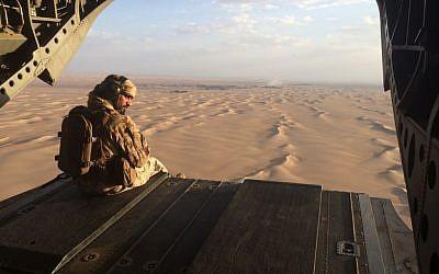 Un artillero emiratí observa el fuego enemigo desde la puerta trasera de un helicóptero militar Chinook de los Emiratos Árabes Unidos sobrevolando Yemen. (AP Photo / Adam Schreck, Archivo)