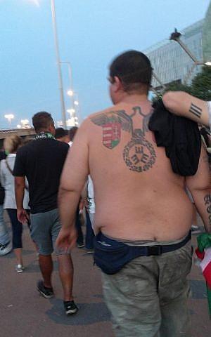 Un hombre con un tatuaje en la espalda que se asemeja al Reichsadler, el símbolo oficial de la Alemania nazi, fuera del Groupama Arena en Budapest, después de un partido entre el club local Ferencvaros Torna y el Maccabi Tel Aviv. (Yaakov Schwartz / Times of Israel)