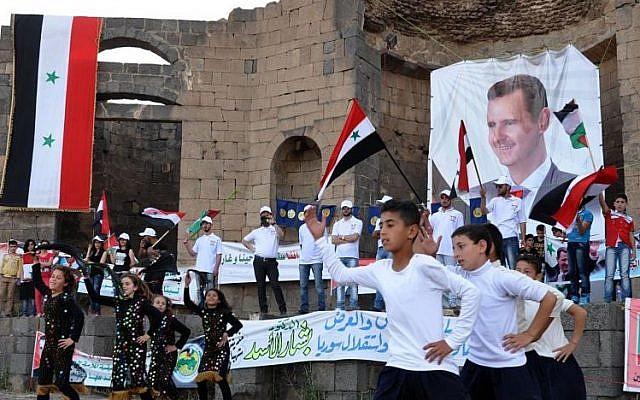 Los partidarios del presidente sirio Bashar Assad sostienen sus retratos y agitan banderas sirias durante una manifestación en apoyo de su candidatura a las elecciones presidenciales en la ciudad de Suweida, al sur de Siria, el 31 de mayo de 2014 (Foto: AP Photo / SANA)