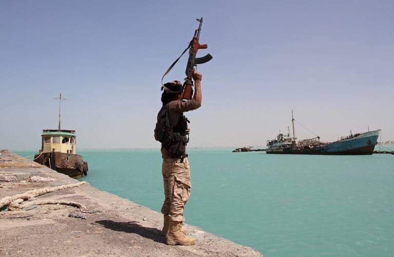 En esta foto de archivo tomada el 8 de febrero de 2017, un miembro de las fuerzas progubernamentales levanta su arma en el puerto de la ciudad costera de Mokha, en el oeste de Yemen, mientras las tropas respaldadas por Arabia avanzan en un intento de conducir a los shiitas Houthis lejos de la costa del Mar Rojo.(AFP Photo / Saleh al-Obeidi)
