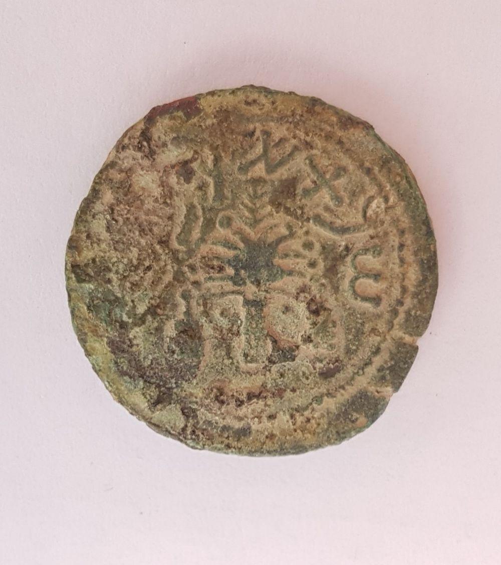 Una extraña moneda de bronce del año cuatro, acuñada en 69-70 EC durante la Gran Revuelta Judía, descubierta en el tamizado en húmedo del material de la Ciudad de David, junio de 2018. (Ilan Shilmaiv / Ciudad de David)