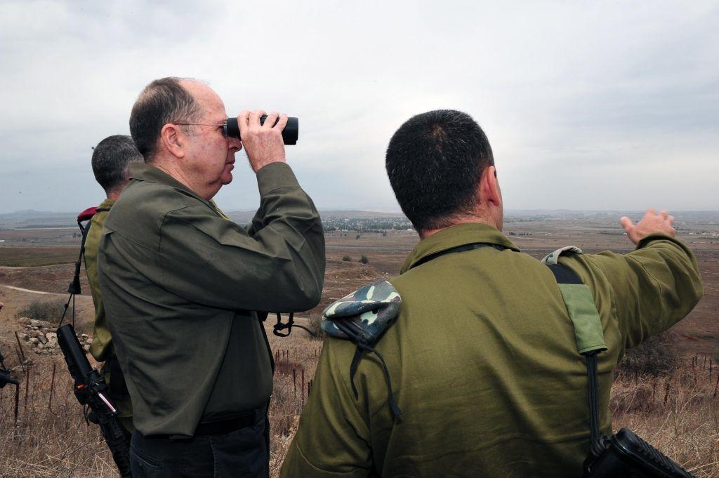 El entonces ministro de Defensa Moshe Ya'alon observa el territorio sirio desde los Altos del Golán el 3 de diciembre de 2013. (Crédito de la foto: Ariel Hermoni / Ministerio de Defensa / Flash 90)