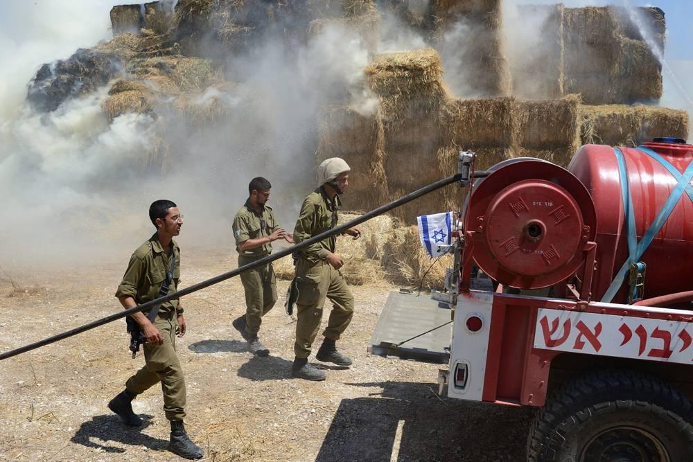 Los bomberos y los equipos de seguridad combaten un incendio en un establo, causado por una cometa cargada con un artefacto incendiario desde Gaza, en el Kibbutz Nahal-Oz el 21 de julio de 2018. (Gili Yaari / FLASH 90)