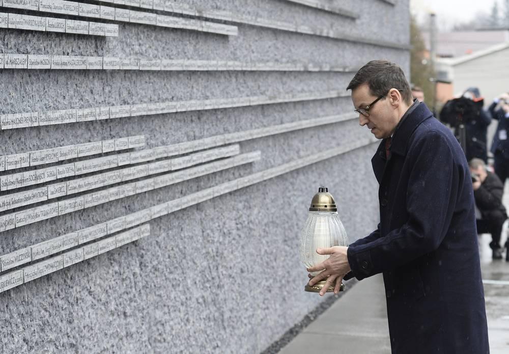El primer ministro polaco Mateusz Morawiecki coloca una vela en una pared conmemorativa con los nombres de algunos de los polacos que salvaron judíos durante el Holocausto, en el Museo de la Familia Ulma que rescató a judíos durante la Segunda Guerra Mundial, en Markowa, Polonia, el viernes 2 de febrero. 2018. (AP / Alik Keplicz)