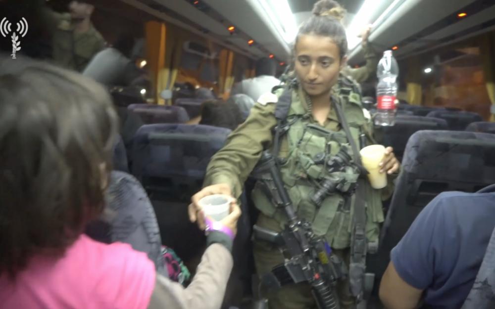 Soldados de las FDI dan agua a los trabajadores de rescate de 'Casco Blanco' y a sus familias, que Israel transportó desde Siria a Jordania, cuando huyen del régimen de Assad, el 22 de julio de 2018. (Fuerzas de Defensa de Israel)
