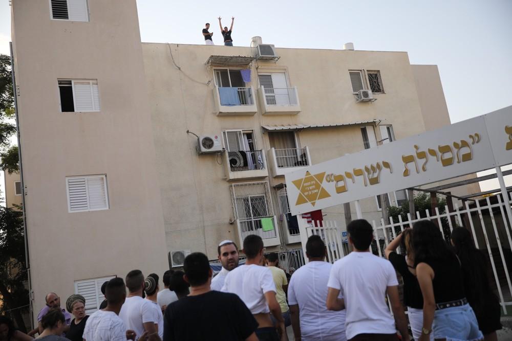 Personas en la escena en que un edificio fue alcanzado por un cohete en la ciudad de Sderot, en el sur de Israel, durante una escalada de disparos de cohetes desde Gaza sobre las ciudades israelíes, el 14 de julio de 2018. (Hadas Parush / Flash 90)