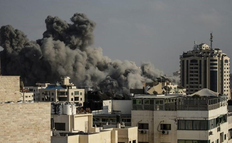 El humo se eleva sobre los edificios durante un ataque aéreo israelí en la ciudad de Gaza el 14 de julio de 2018. (AFP PHOTO / MAHMUD HAMS)