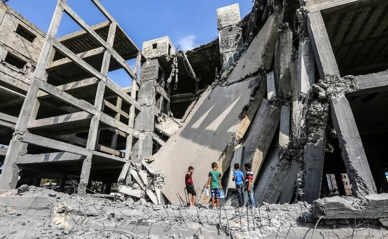 Niños palestinos caminan a través de los restos de un edificio de Hamas que fue dañado por los ataques aéreos israelíes en la ciudad de Gaza el 15 de julio de 2018. (AFP / MAHMUD HAMS)