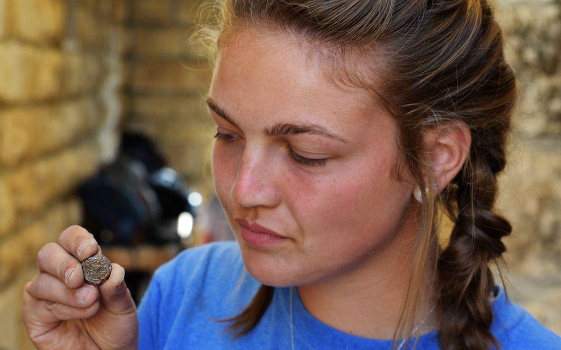 Una estudiante de Armstrong College tiene una moneda descubierta en la excavación arqueológica de Ophel fuera de las murallas de la Ciudad Vieja de Jerusalem, donde recientemente se descubrió un alijo de raras monedas de bronce de la Revuelta Judía, que data de alrededor del 66-70CE.(Eilat Mazar)