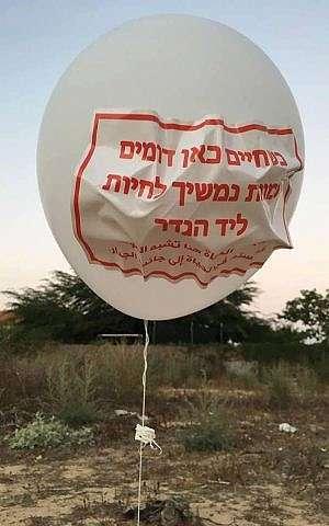 Un globo lanzado desde la Franja de Gaza que aterrizó dentro de la región del sur de Israel Eshkol, leyendo, Mientras la vida aquí es como la muerte, seguiremos viviendo cerca de la valla, el 12 de julio de 2018. (Seguridad Eshkol)