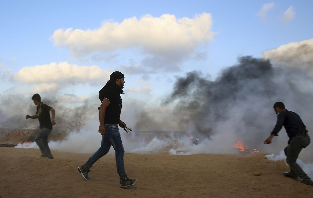 Los islamistas intentan arrojar gases lacrimógenos disparados por las tropas israelíes cerca de la valla de la Franja de Gaza con Israel, durante una violenta manifestación al este de Khan Younis, al sur de la Franja de Gaza, el viernes 20 de julio de 2018 (AP Photo / Adel Hana)