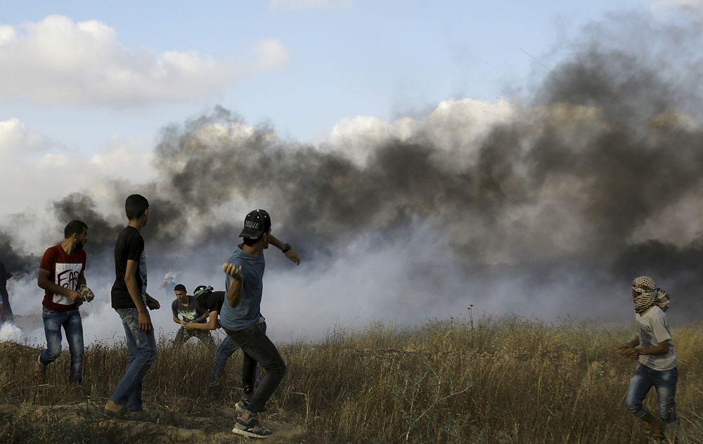 Un islamista palestino arroja piedras a las tropas israelíes después de quemar neumáticos cerca de la frontera de la Franja de Gaza con Israel, durante una manifestación islamista al este de Khan Younis, en la Franja de Gaza el 1 de junio de 2018. (AP Photo / Adel Hana)