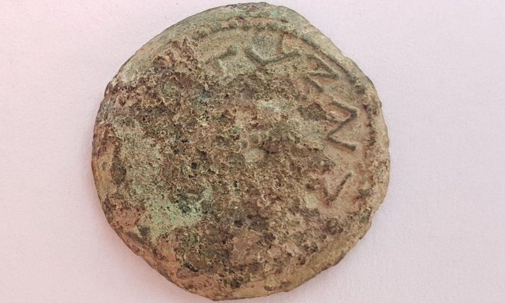 Una extraña moneda de bronce del año cuatro, acuñada en 69-70 EC durante la Gran Revuelta Judía, inscrita con 'Por la redención de Sión', fue descubierta en el tamizado húmedo de material de la ciudad de David, junio de 2018. (Ilan Shilmaiv / City de David)