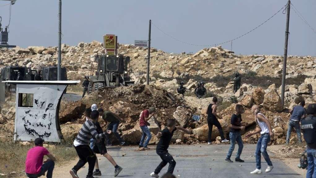 Islamistas palestinos atacan a los soldados israelíes, mientras un bulldozer del ejército cierra la carretera principal con tierra durante su operación para registrar la casa familiar de Omar al-Abed, 20, 22 de julio de 2017. (Foto AP / Nasser Nasser)